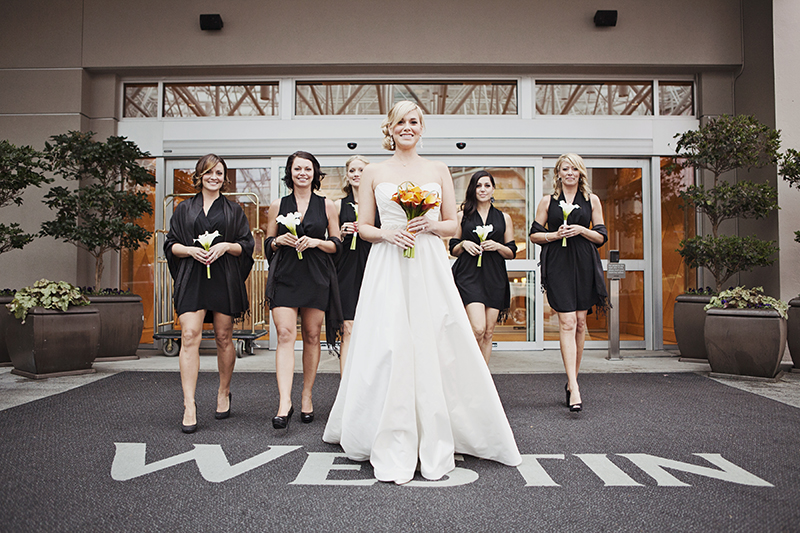 bride walking out of hotel with bridesmaids