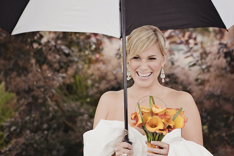 bride laughing under umbrella