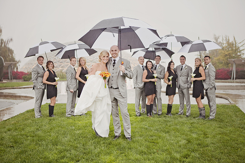 rainy day wedding party portrait with umbrellas