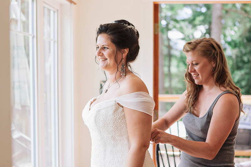 maid of honour doing up brides dress