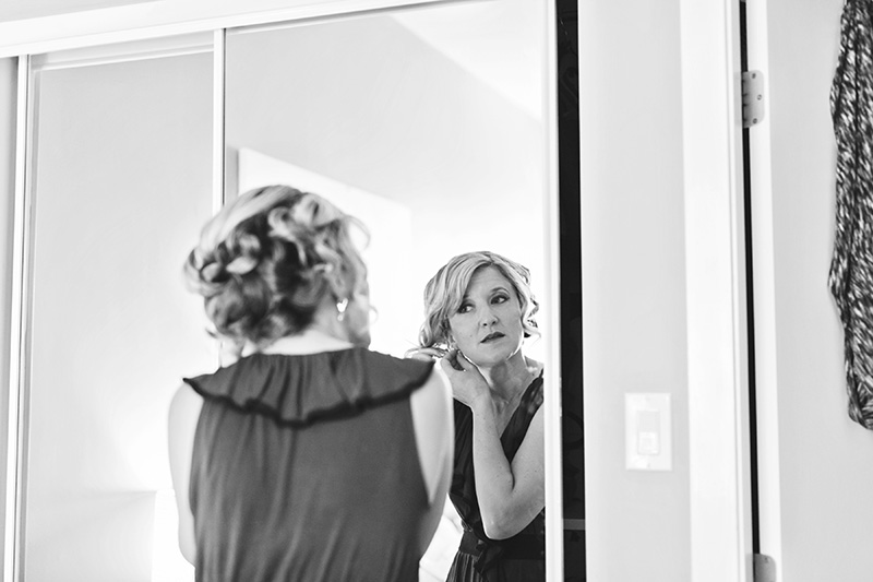 bride looking in mirror while putting in earring