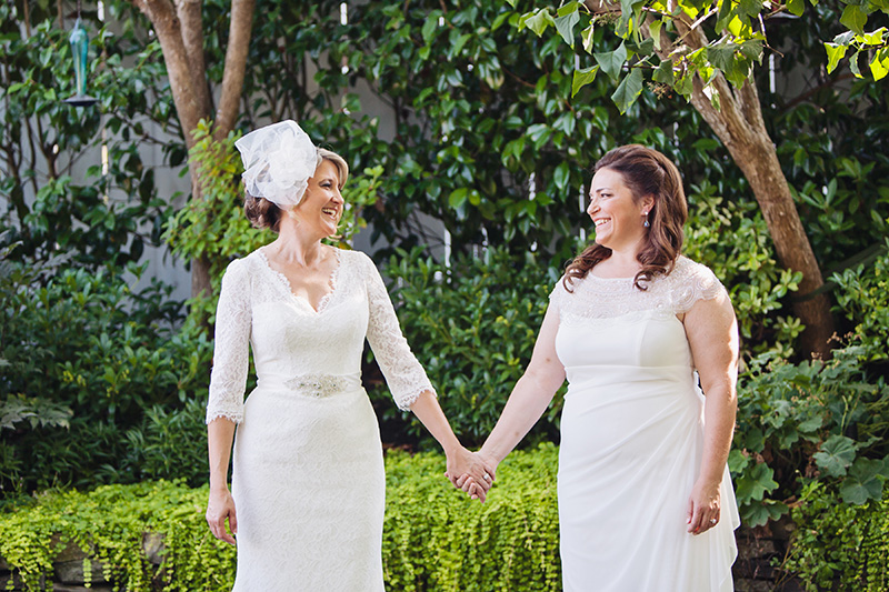 two brides holding hands in garden