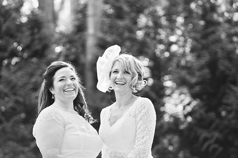 two brides laughing in front of trees