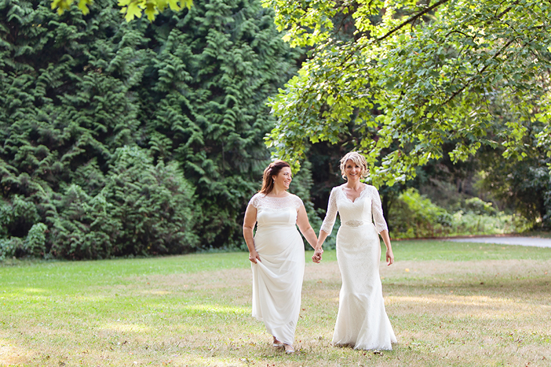 two brides walking across grass