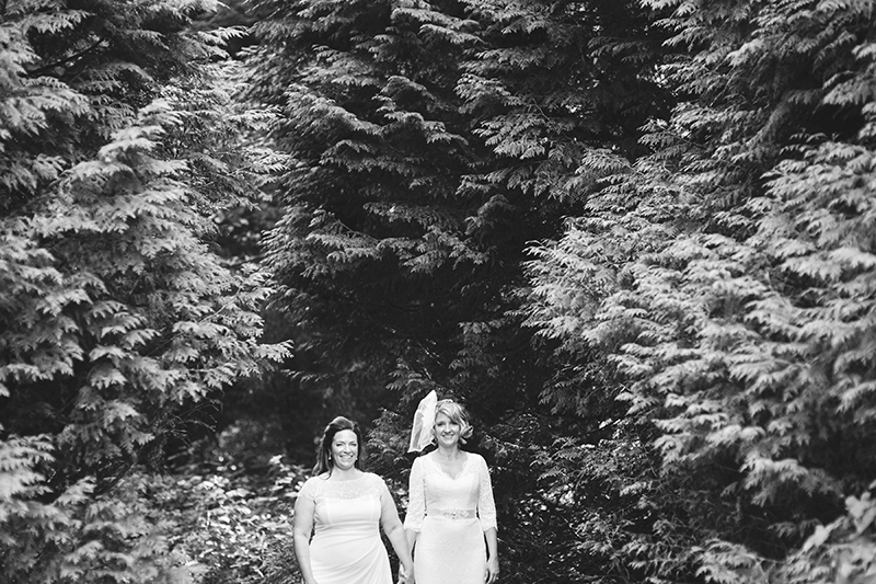 two brides in front of trees