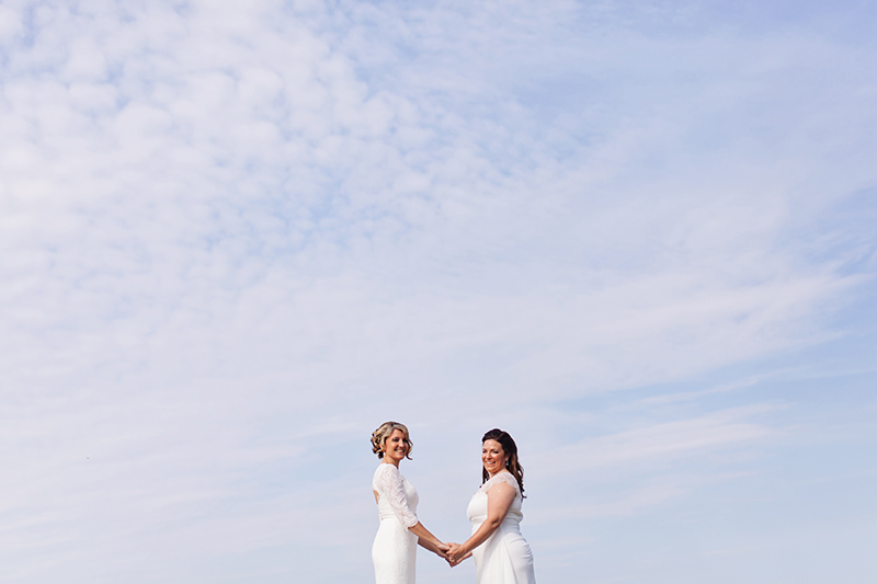 two brides holding hands in front of blue sky