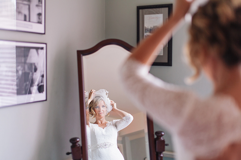 bride fixing fascinator in mirror