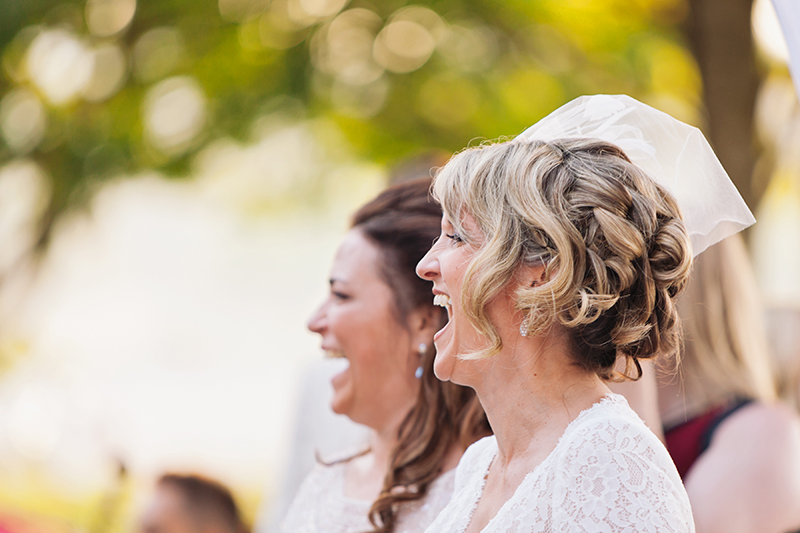 two brides laughing during wedding ceremony
