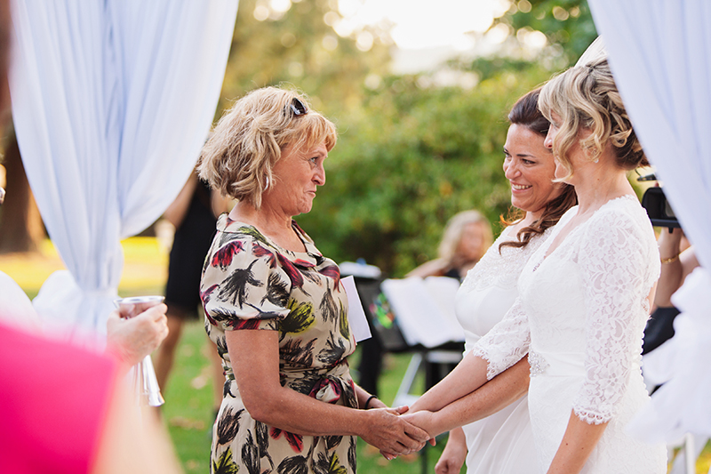 aunt blessing two brides during wedding ceremony