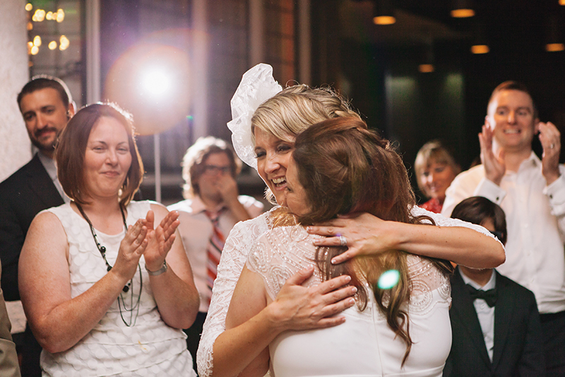 two brides hugging on dance floor