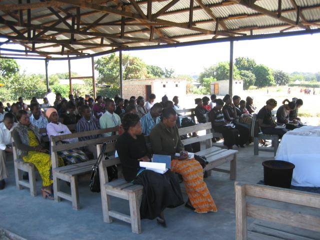Church members in rural Zambia enjoy Mulenga preaching a Sunday sermon.