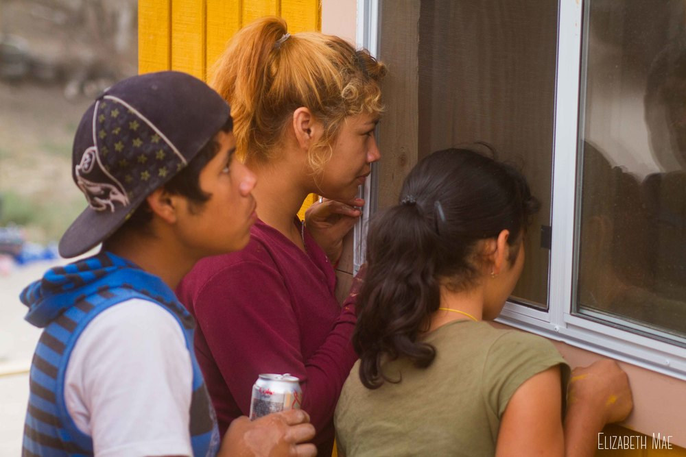 Rebeca looks into her home with her siblings