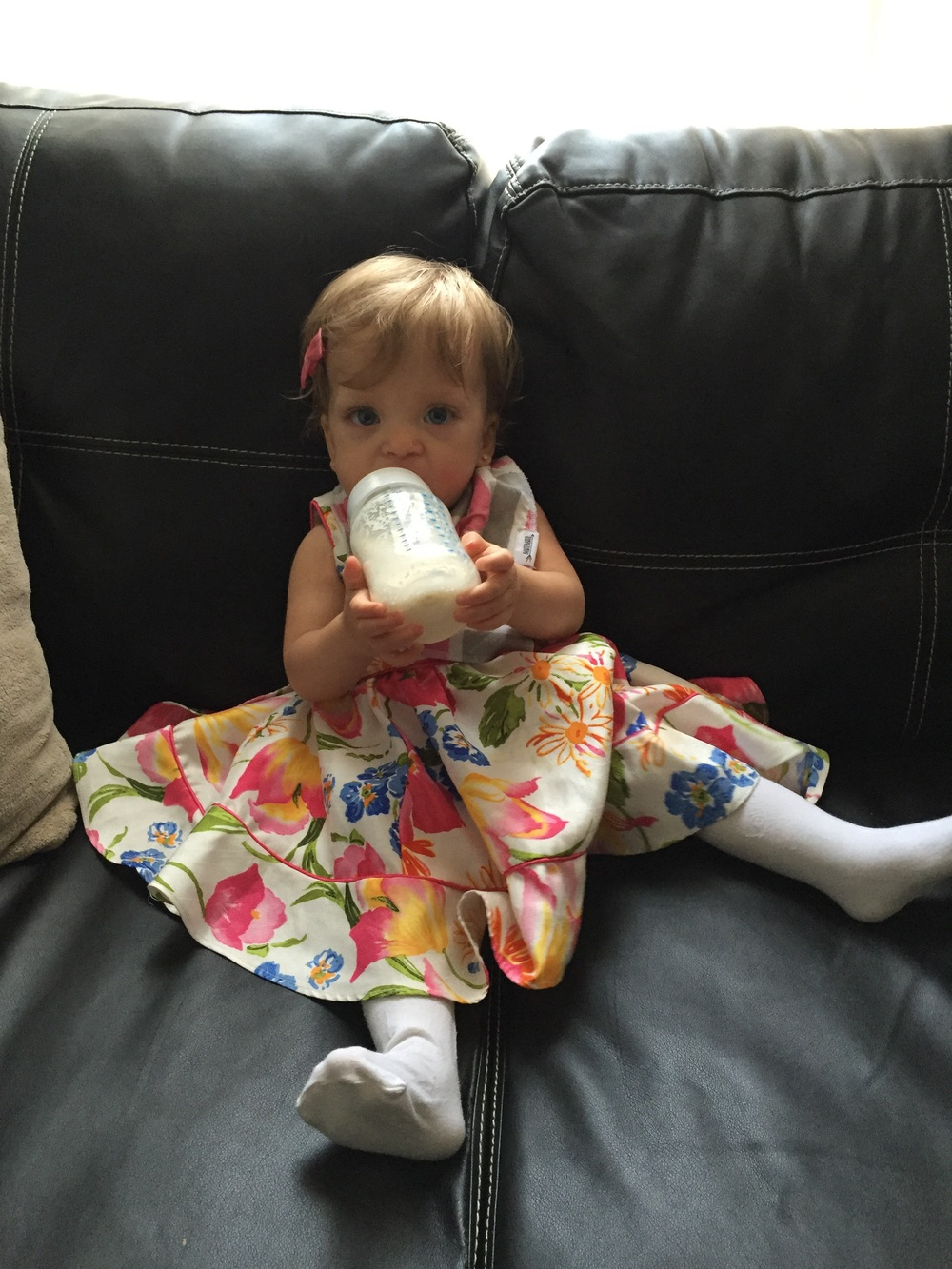 Figuring out how to take her bottle while sitting.