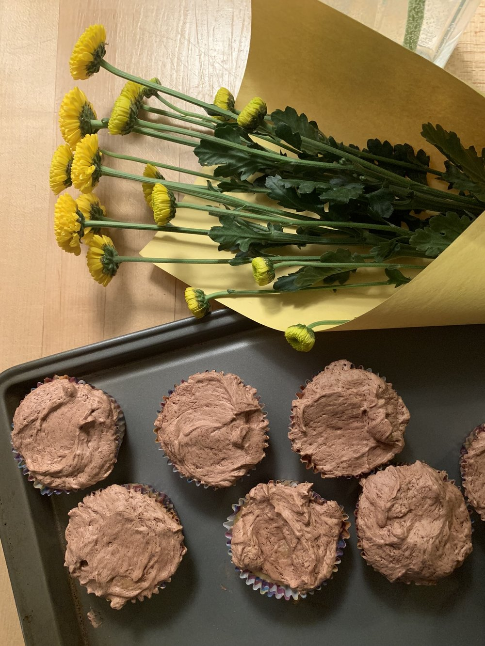 Homemade cupcakes, homemade chocolate frosting and happy yellow flowers that we gave to our neighbors in our building.