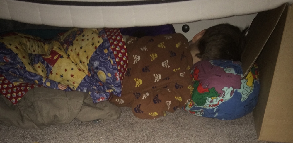 Sleeping under a mattress propped a foot off the ground with cardboard boxes