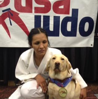Christella with her guide dog, Priscilla, proudly wearing her competition medal!