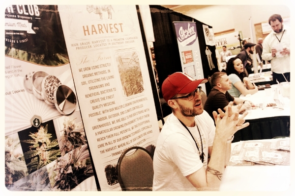 TRAVIS ASHLEY, WITH HIGH GRADE HARVEST IN TALENT, CHATS WITH CONFERENCE ATTENDEES DURING THE OREGON MEDICAL MARIJUANA BUSINESS CONFERENCE SUNDAY AT THE HILTON EUGENE. THE MARIJUANA INDUSTRY IS PREDICTED TO GROW BY 32 PERCENT THIS YEAR. (AMIRAN WHITE/ FOR THE REGISTER-GUARD)