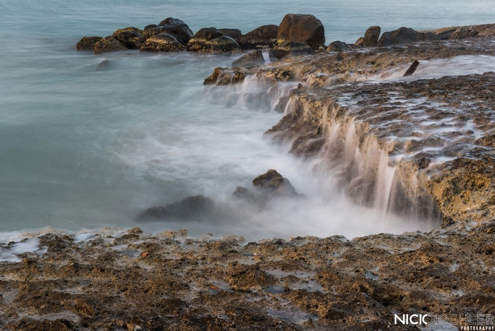 The rocky coast drew my eye when I saw the waves crashing and leaking through the cracks.