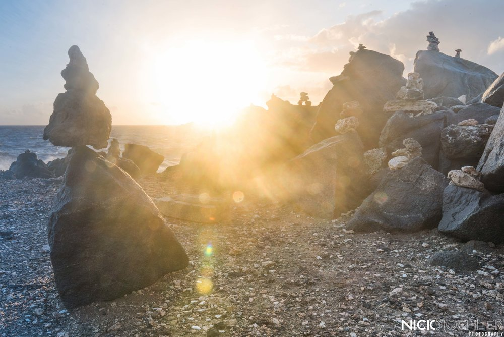 Beautiful sunrise shooting through stacked rocks.