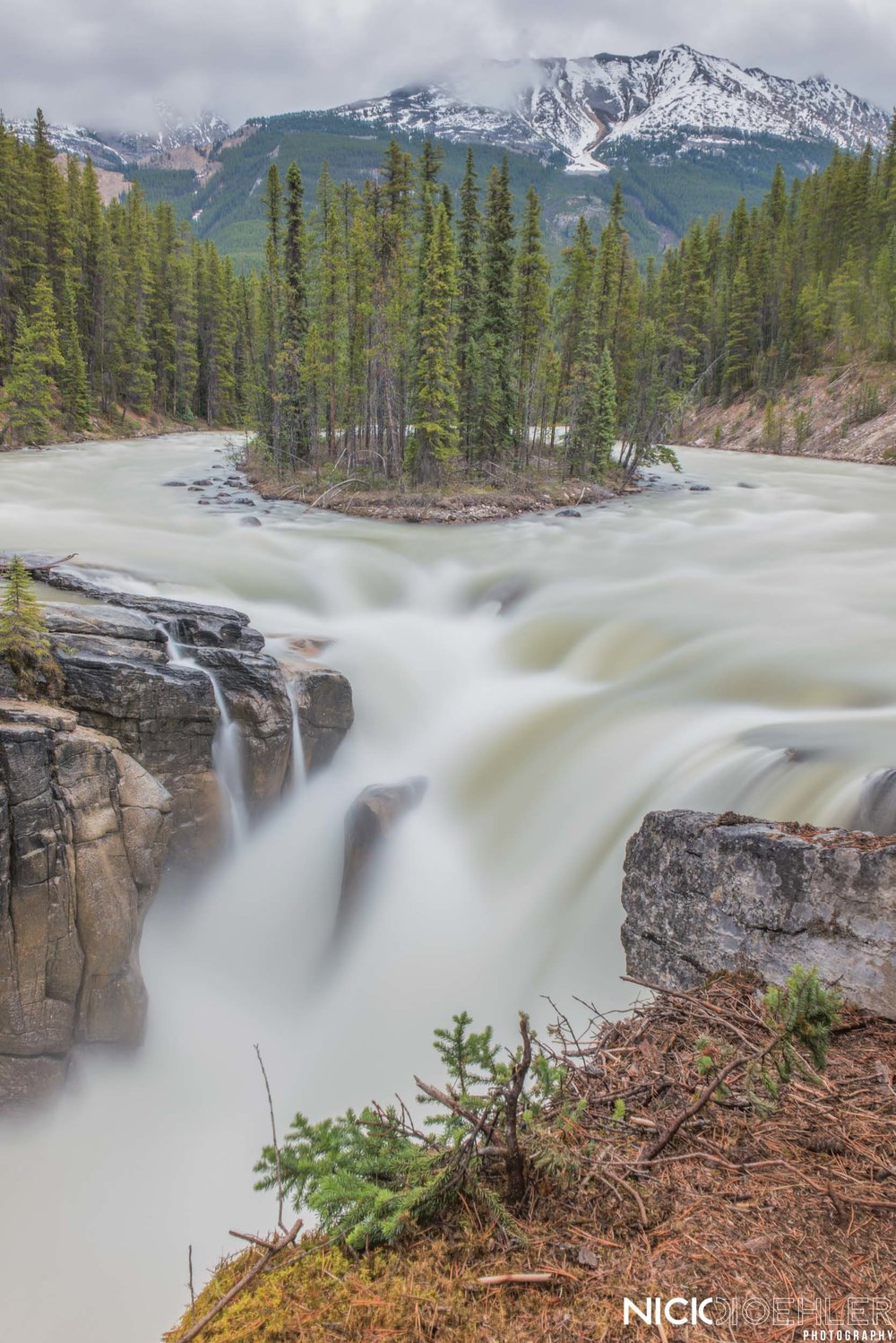 Jasper National Park: A raging waterfall being fed by a beautifully shaped river.