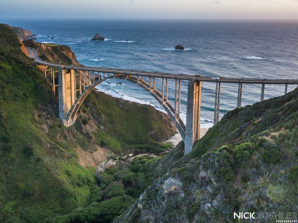 Big Sur: A drone shot of a beautiful curved bridge during sunset.
