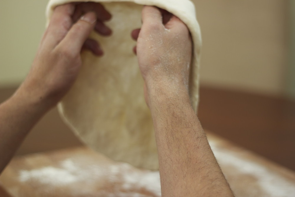 Gently begin rotating and stretching the dough with the back of your knuckles.
