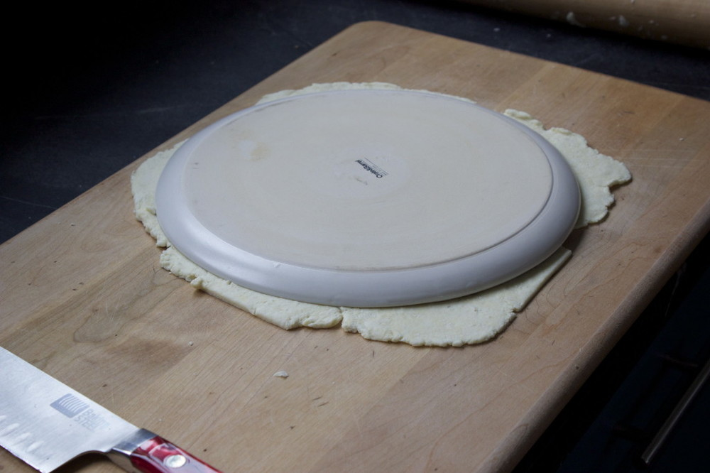 cutting out a round gluten free pizza crust