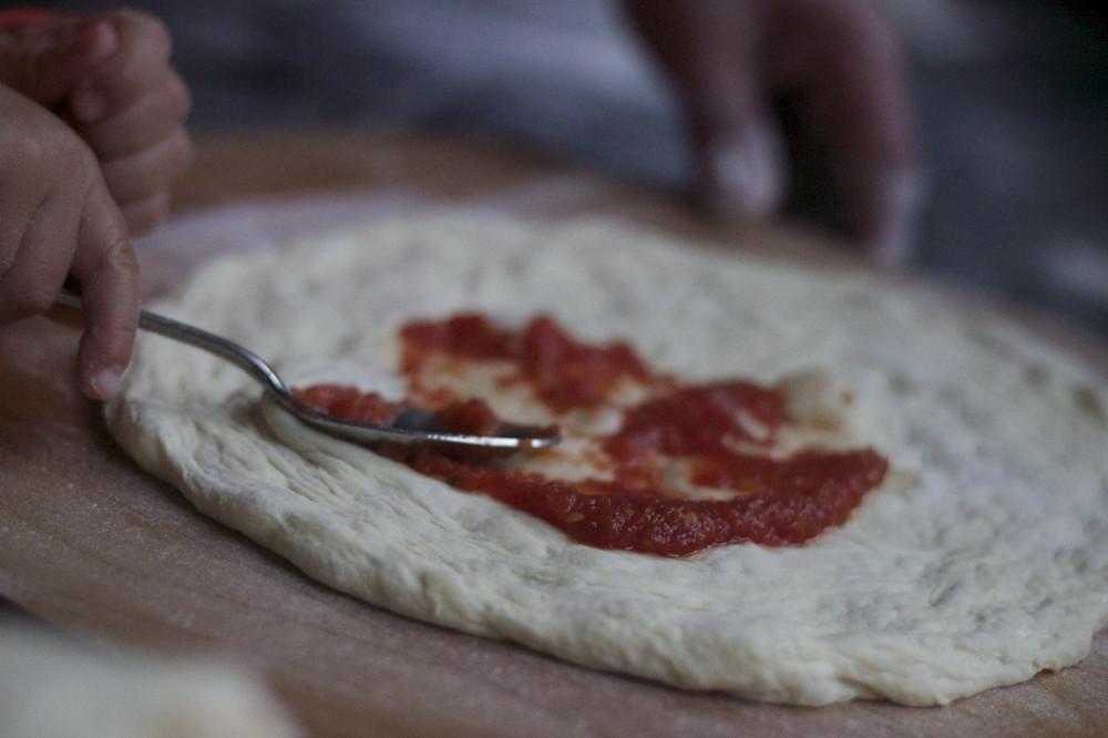 tomato saucing the dough