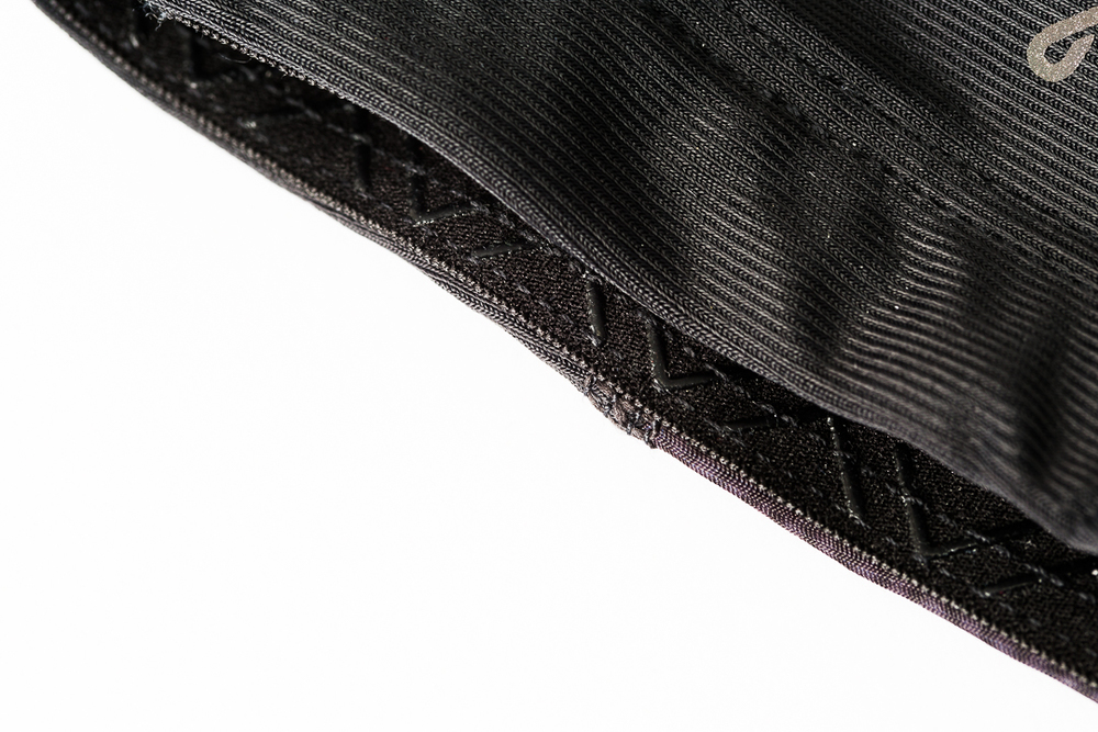 Black herringbone patterned silicone on the lower hem of the Kitsbow knee warmers for road cycling.