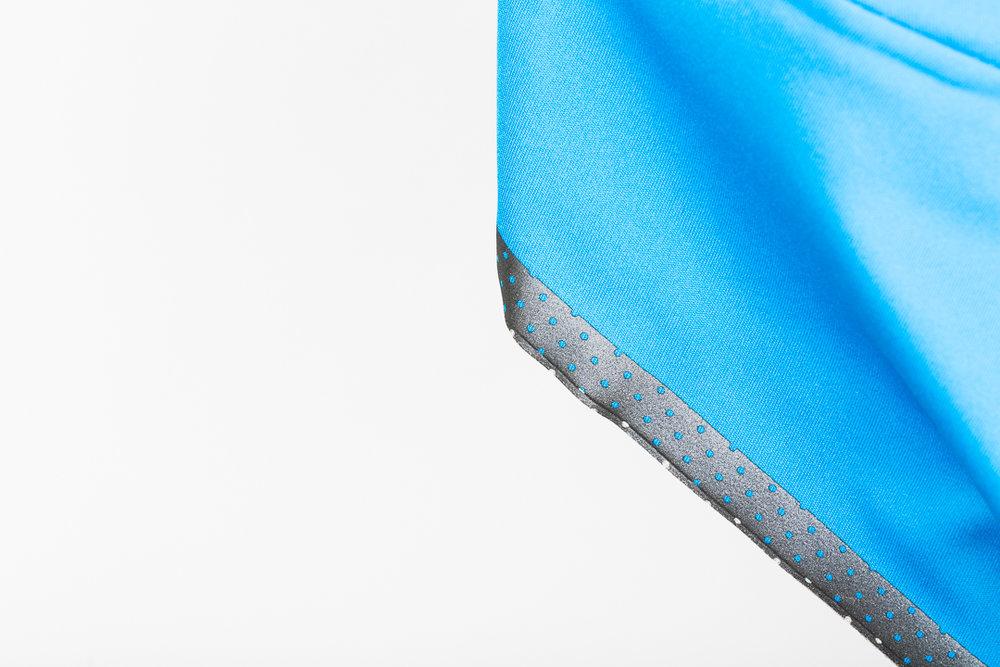 The gunmetal reflective bottom hem of the7mesh Corsa Softshell Jersey retains 75% the luminance of full silver.