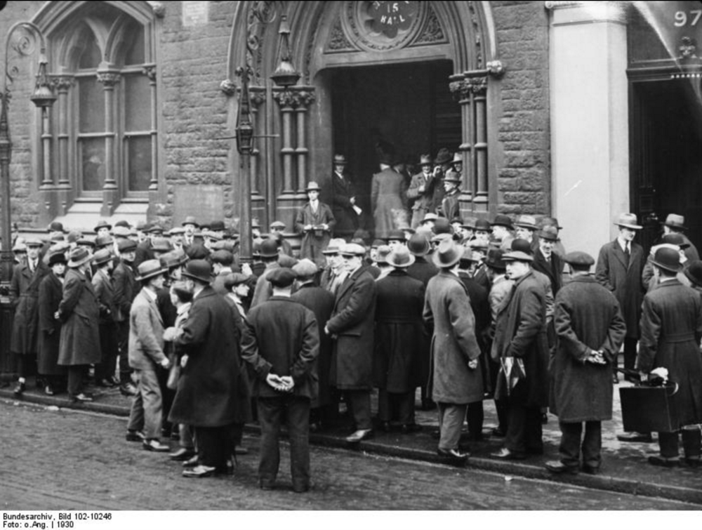 Unemployed people in front of a workhouse in London, 1930. Image attributed to: Bundesarchiv, Bild 102-10246 / CC-BY-SA 3.0. Source Wikipedia Commons