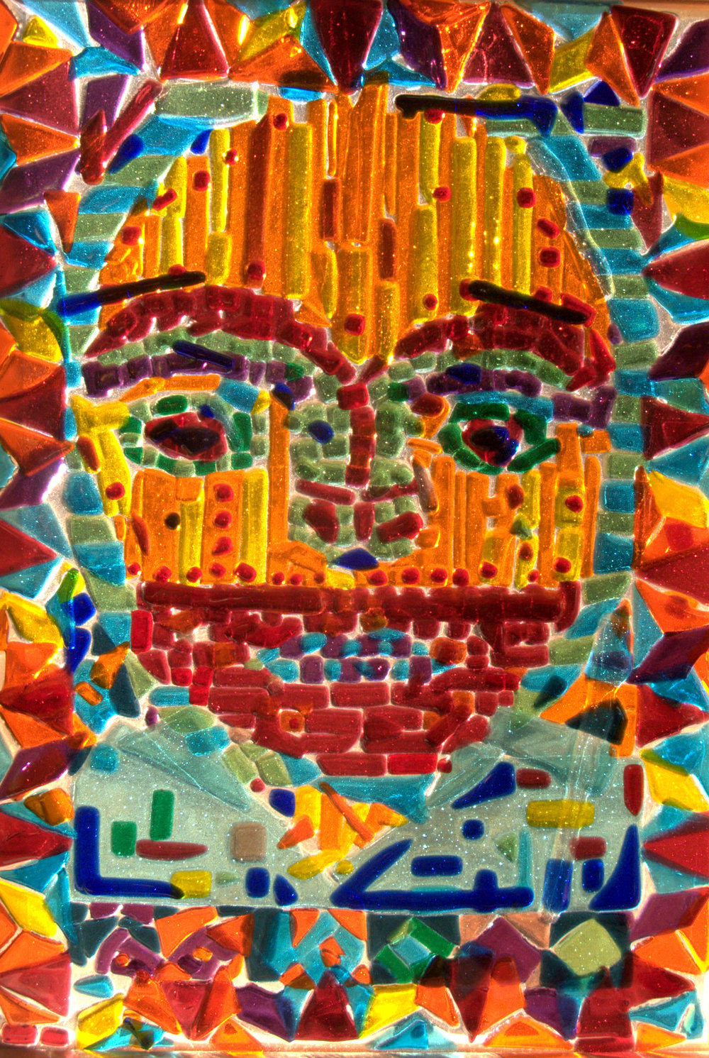 Inspired by an African mask.   I had seen a photo of an African mask which I liked and thought I'd do something like it.   I added my own patterns ont he edge.  2010  Fused glass.