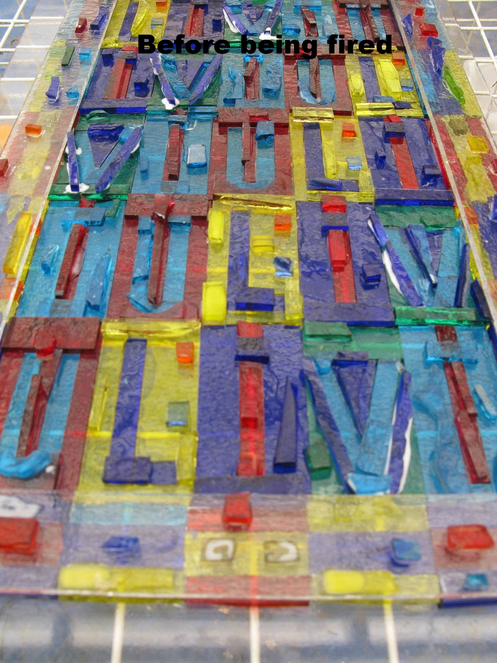 Play on the letters 'Liviu,' which are rotated around.  The glass before being fired.   You would not want to leave the glass as is because it would not permanently adhere to the base white glass it is on.  2010  Fused glass.