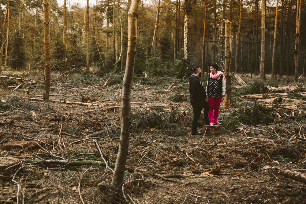 Loveshoot where couple is standing in the middle a raw forrest