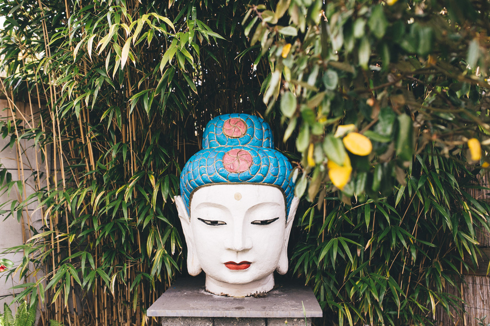 Head of a buddha in a garden during the first look