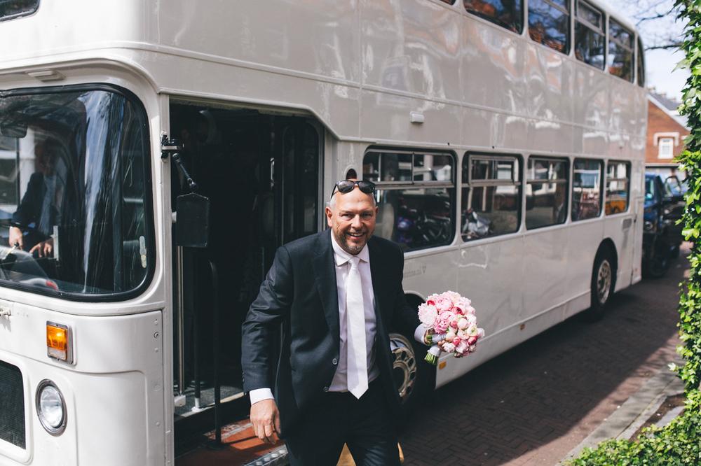 Bruidegom stapt uit de witte londonse dubbeldekker