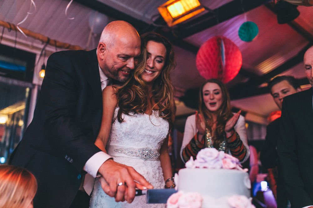 Cutting of the cake by wedding photographer at beachclub