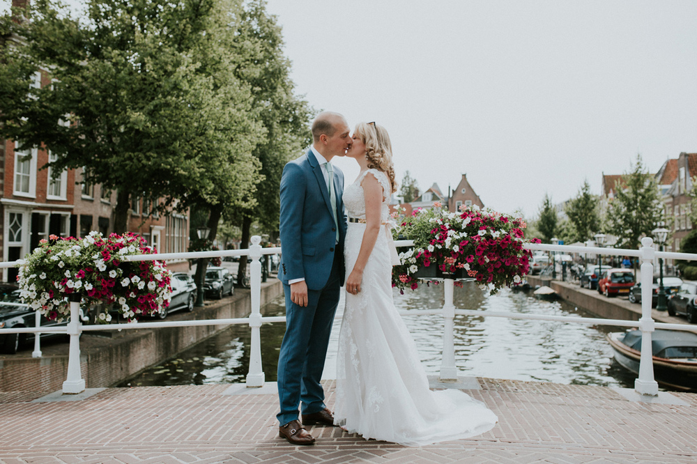 bride and groom kissing on a bridge in amsterdam