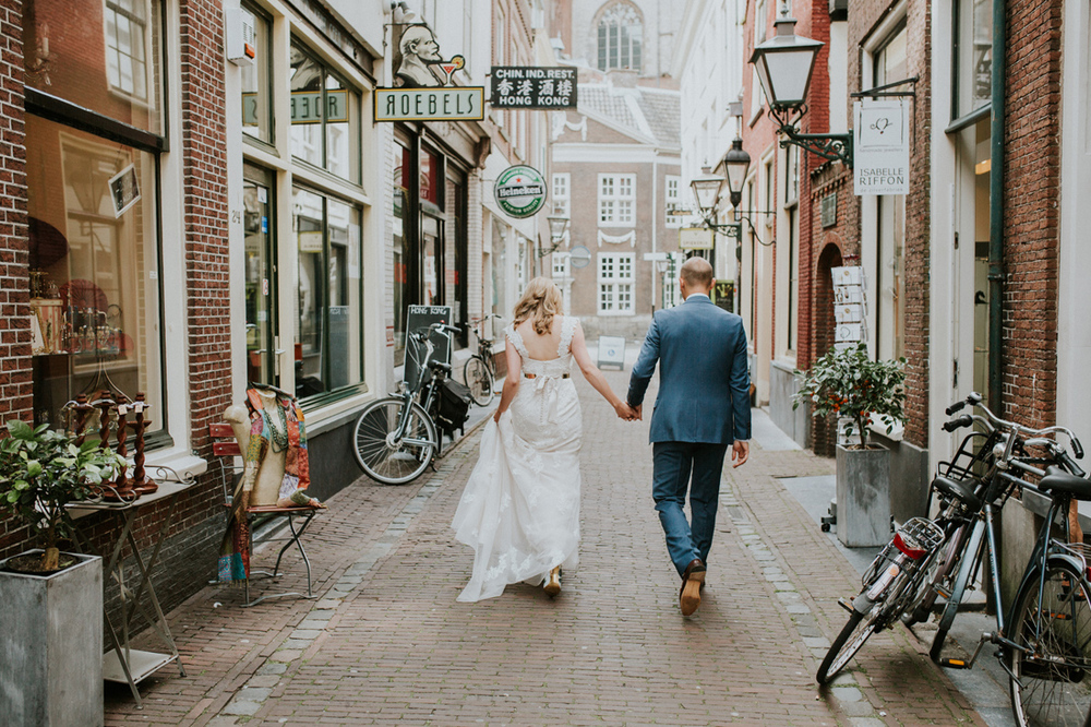 Bride and groom walking through the center of leiden