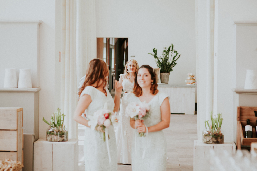bride with bridesmades walking down the aisle