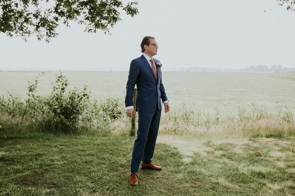 groom waiting in meadow