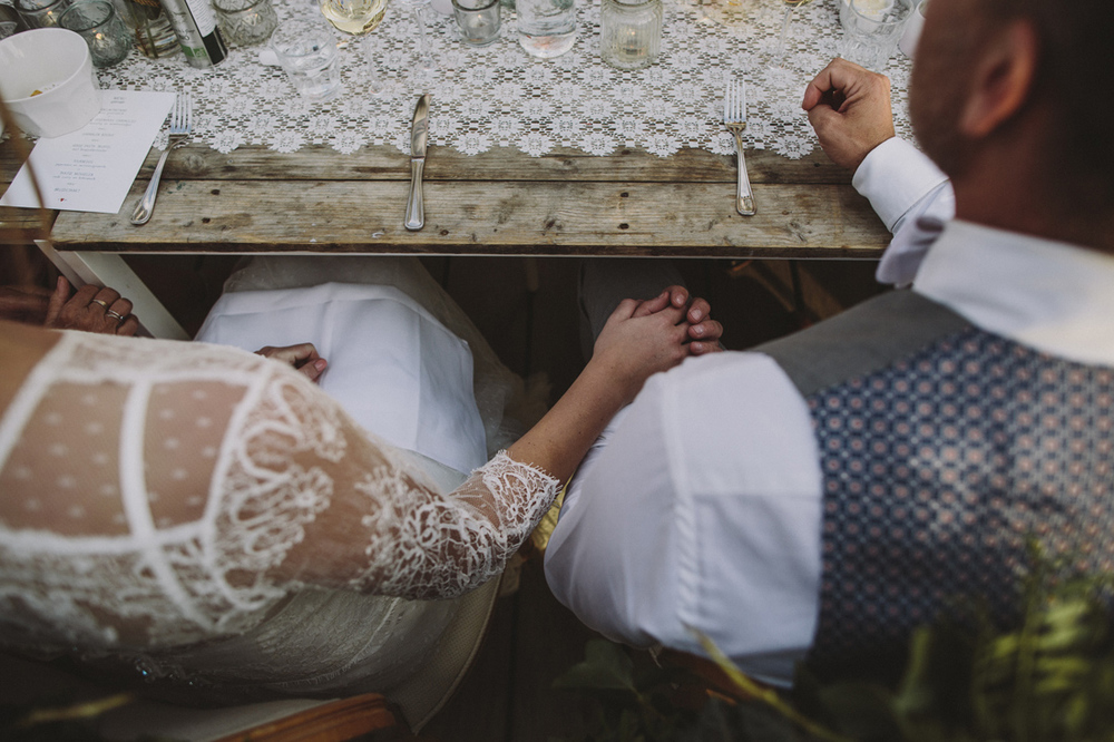 Holding hands at wedding at vintage table