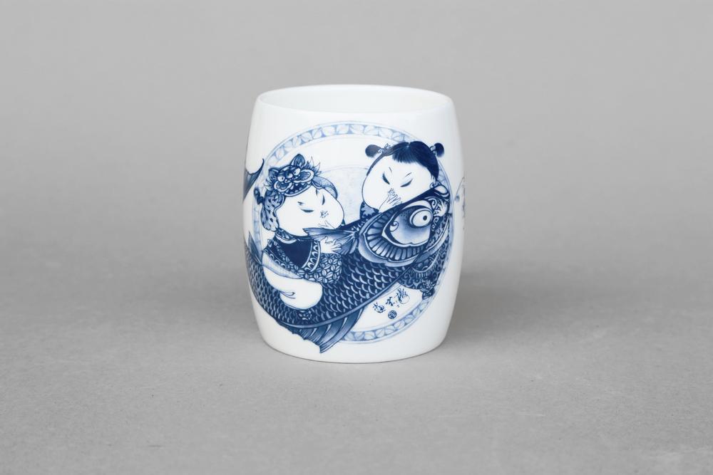 兩個胖娃娃與招財魚,身材都很圓潤富貴,大魚即為「有餘」,象徵夫婦之情 「 富貴有餘 」 。   楊莉莉青花:富貴有魚大福杯   尺寸(頂直徑 x 底直徑 x 高):8.0 x 8.0 x 10.0 cm 容量:400 ml 材質:陶瓷 產地:台灣 包裝:棕黃牛皮紙盒 建議售價:590 元 備註:本產品有杯耳 庫存狀態:正常供應