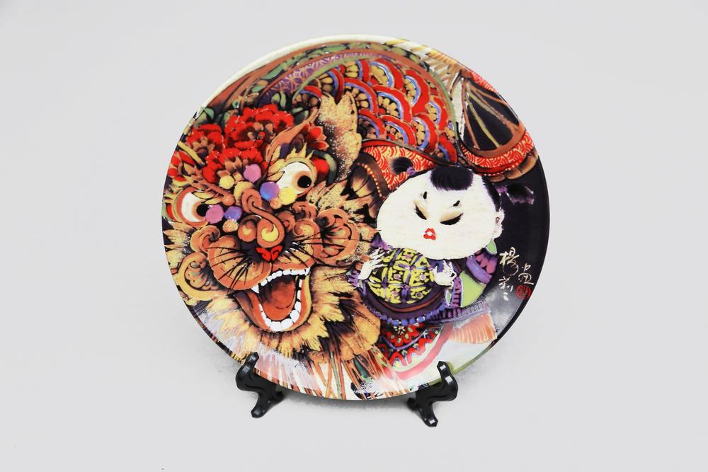 在宋朝時期,瓷器產業已經十分發達,在燒製瓷上畫也有相當的技術。明清時期,瓷上畫的種類發展到了極致,畫家開始在瓷器上作畫題詩,提高了它的藝術品味,於是也就產生了瓷盤畫。  此一兼具古典與現代風格的瓷盤畫商品,由楊莉莉所創作之原畫,製作印花燒製而成。一只手舞戲龍,一只綵球弄獅。民俗年獸與雙娃的友誼,就如青梅竹馬般天真無邪,輝映著色彩絢麗的童趣時光。   楊莉莉青花:綵球獅八吋瓷盤畫   尺寸(直徑 x 直徑 x 高):20.5 x 20.5 x 2.0 cm 材質:陶瓷 產地:台灣 包裝:紅黑禮盒 建議售價:990 元 庫存狀態:已售完