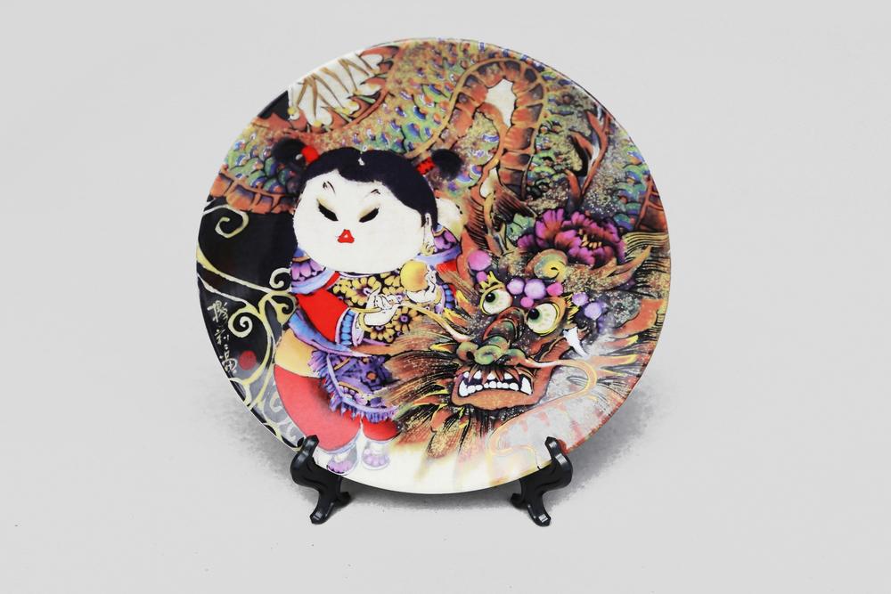 在宋朝時期,瓷器產業已經十分發達,在燒製瓷上畫也有相當的技術。明清時期,瓷上畫的種類發展到了極致,畫家開始在瓷器上作畫題詩,提高了它的藝術品味,於是也就產生了瓷盤畫。  此一兼具古典與現代風格的瓷盤畫商品,由楊莉莉所創作之原畫,製作印花燒製而成。一只手舞戲龍,一只綵球弄獅。民俗年獸與雙娃的友誼,就如青梅竹馬般天真無邪,輝映著色彩絢麗的童趣時光。   楊莉莉青花:龍女圖八吋瓷盤畫   尺寸(直徑 x 直徑 x 高):20.0 x 20.0 x 2.0 cm 材質:陶瓷 產地:台灣 包裝:紅黑禮盒 建議售價:990 元 庫存狀態:正常供應