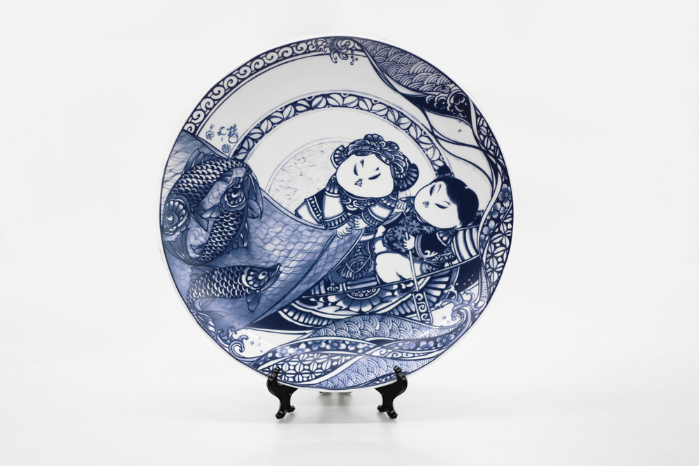 胖娃娃與招財魚,都是體形豐滿者,魚的諧音即為「餘」,有富貴有餘的意義外,兩人為家庭共同打拚的夫妻之情,有餘且知足,更是感情恆長的象徵。   楊莉莉青花:滿載而歸十二吋瓷盤畫   尺寸(直徑x直徑x高):30.5 x 30.5 x 4.0 cm 材質:陶瓷 產地:台灣 包裝:紅黑禮盒 建議售價:2390 元 庫存狀態:正常供應
