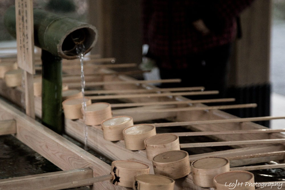 Visitors wash their hands before entering the shrine using these