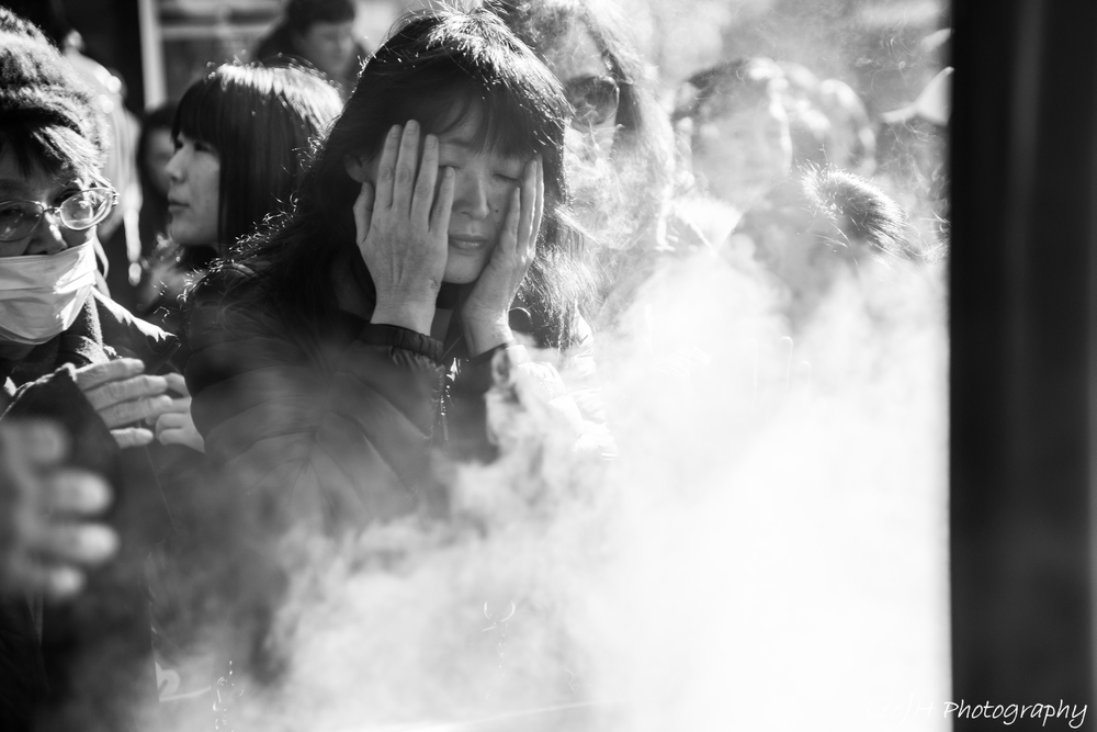 """Visitors """"washing"""" themselves with incense smoke before entering the shrine"""