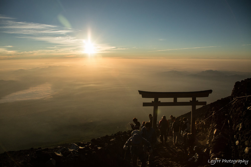 People making their way past the torii gate that marks the end of the climb, with the sunrise in the background.