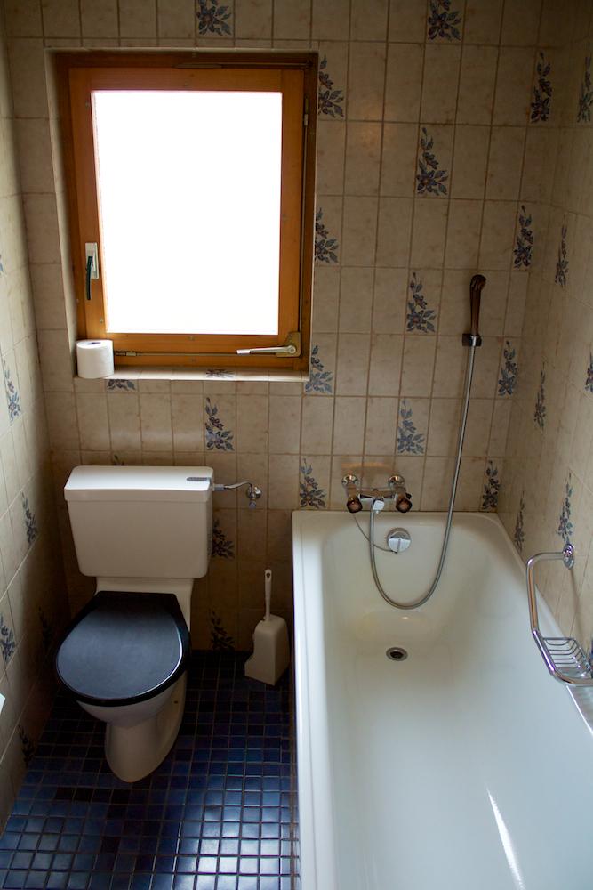 Badkamer met ligbad, wc en wastafel.